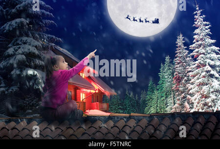 Girl sits on the roof in The Christmas eve pointing to the sky - Stock Photo