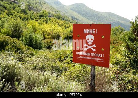 Land mine warning sign on the boder of Republika Srpska and Federation of Bosnia and Herzegovina near Zavala in - Stock Photo