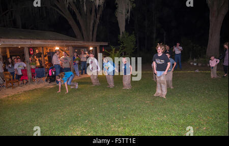 Kids in a sack race during a fall celebration in North Central Florida. - Stock Photo