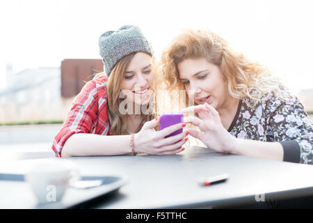 Two young curly and straight blonde hair caucasian woman sitting on a bar, using smartphone, both looking downward - Stock Photo