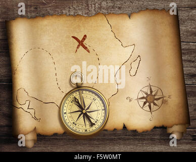 treasure map roll with old compass on table top view - Stock Photo