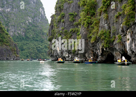 Tourists on wooden row boats amid limestone (karst) mounds, Vung Vieng fishing village, Ha Long Bay, Bai Tu Long - Stock Photo