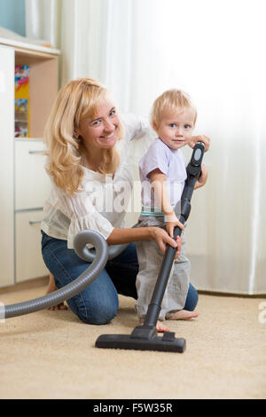 family have fun with cleaning carpeting - housework - Stock Photo