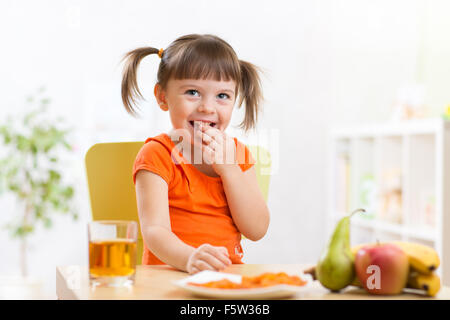 Smiling girl sitting on the table with fruits and juice - Stock Photo