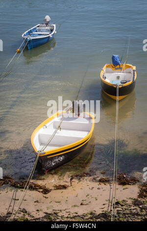 Three small outboard motorboats moored on a beach in Cornwall, UK - Stock Photo