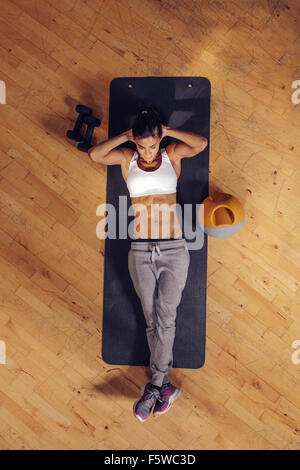 Fit young woman lying on exercise mat doing stomach exercises. Overhead view of female working out at the gym - Stock Photo