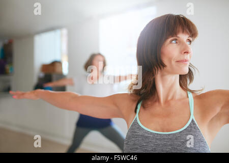 Portrait of beautiful young woman doing the warrior pose during yoga class. Yoga instructor performing Virabhadrasana - Stock Photo