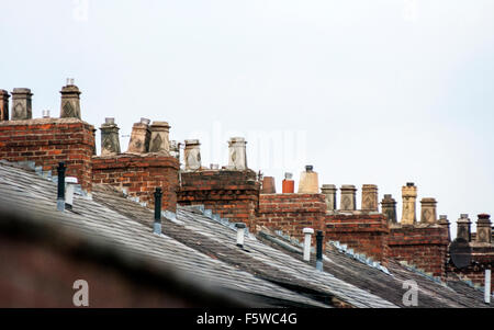 Rooftops and chimneys on a row of terraced houses in Stretford, Manchester, England, UK - Stock Photo