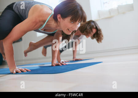 Two women at yoga class doing yoga hand stand pose. Mature woman standing on hands with feet lifted up doing crane - Stock Photo