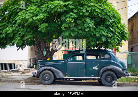 Classic American car parked under a tree in Havana, Cuba - Stock Photo