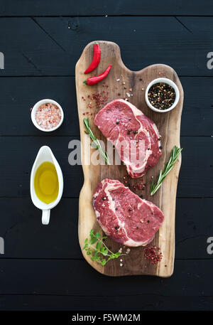 Raw fresh meat Ribeye steak entrecote and seasonings on cutting board on dark wooden background, top view - Stock Photo