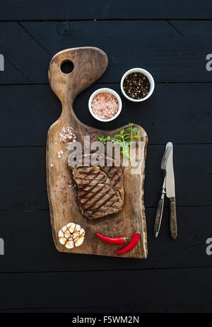 Grilled ribeye beef steak with herbs and spices on walnut cutting board over black wooden background, top view - Stock Photo