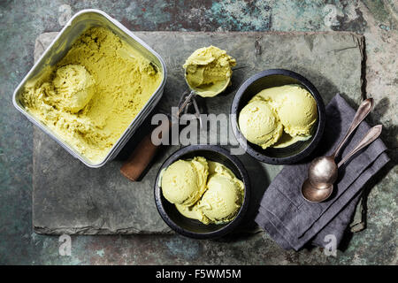 Ice cream Green tea with mint leaves and Spoon for ice cream on stone slate background - Stock Photo