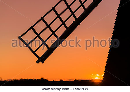 The sail of a windpump at Wicken Fen silhouetted against an orange sky at sunset. [NB. The colour of the sky has - Stock Photo