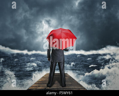 Man with red umbrella standing back on the pier at night storm - Stock Photo