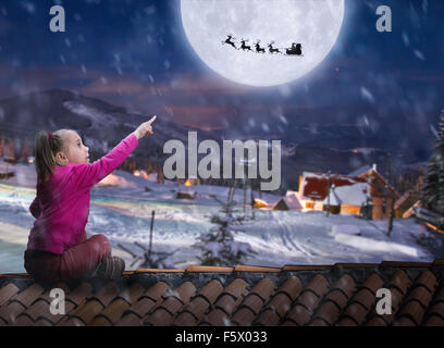 Girl sits on the roof in winter night - Stock Photo