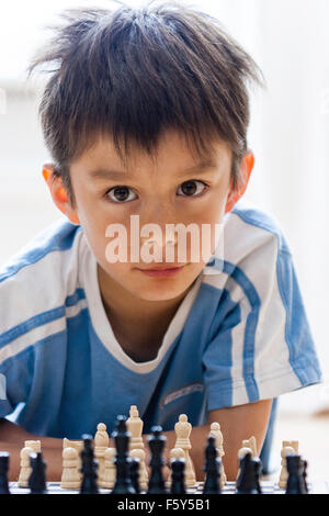 Caucasian child, 7 years old, boy, playing chess game. Straight on view as he looks over the chess pieces and smiles - Stock Photo