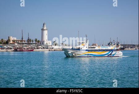 view of La Farola, the lighthouse of the Port of Malaga with a ferry entering the harbour, Costa del Sol, Andalusia, - Stock Photo