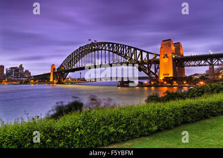 side view of famous Sydney Harbour bridge at sunset with illumination from green recreational park at milsons point - Stock Photo