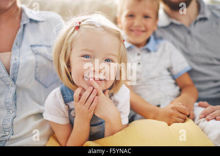 Sweet little girl looking at camera with her parents and brother near by - Stock Photo