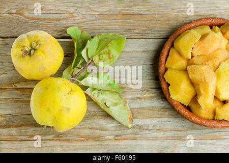 Two quince fruits on wooden background with quince slices on a clay pot - Stock Photo
