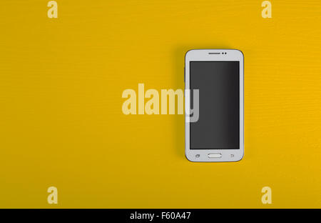 The modern mobile phone with the big touch screen on a yellow wooden background. - Stock Photo
