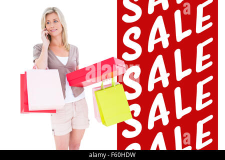 Composite image of happy blonde with shopping bags on the phone - Stock Photo