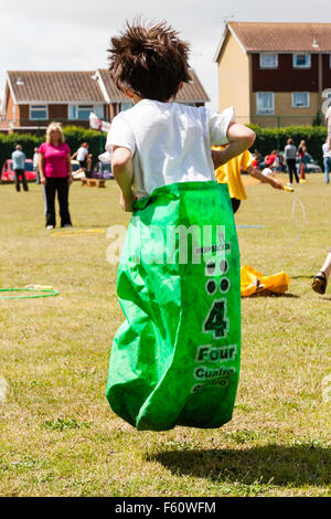 Child, Caucasian, boy, 7-9 years old. Exterior. School sports day. Sack race. Leaping holding sack with both hands. - Stock Photo