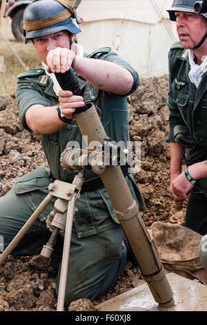 Second world war re-enactment. Two men mortar team in small dugout. one soldier loading 8 cm mortar shell into light - Stock Photo
