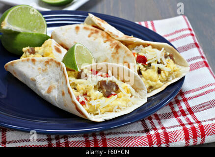 Two breakfast tacos with sausage, cheese, and peppers.  Garnished with fresh lime. - Stock Photo