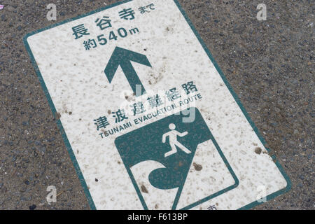 A tsunami evacuation route sign on a pavement in Japan. - Stock Photo