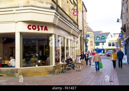 People sitting outside and walking past Costa Coffee on the corner of Meal Market and Fore Street, Hexham, Northumberland, - Stock Photo