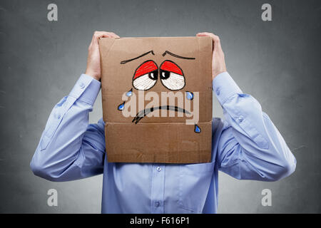 Man with cardboard box on his head showing sad expression - Stock Photo