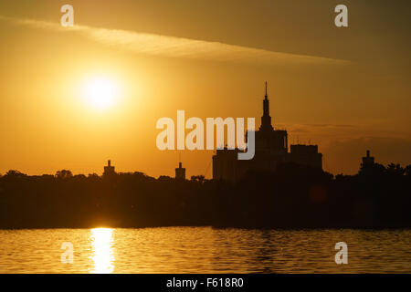 Sunset over Casa Sciintei and the lake at Herastrau Park in Bucharest, Romania. - Stock Photo