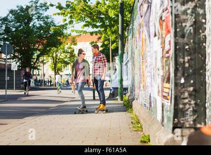 Full length of happy couple skateboarding on sidewalk - Stock Photo