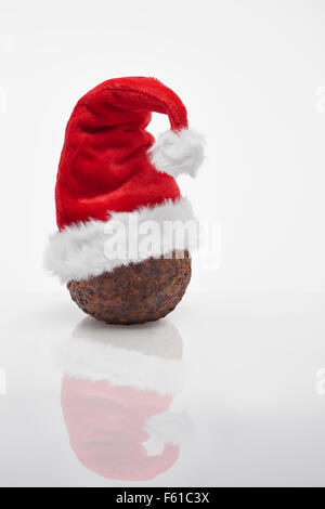 Christmas Pudding with red santa  hat - Stock Photo