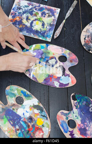 Cropped image of senior woman using palettes while painting - Stock Photo