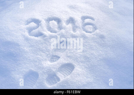 Foot step prints in snow, New Year 2016 greeting - Stock Photo