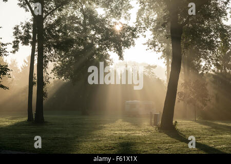 A campsite and caravan in the mist at dawn in France - Stock Photo