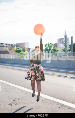 young handsome caucasian redhead woman jumping, playing with orange balloon, hand on her hips, looking up - youth, - Stock Photo