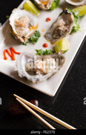 Angled view of oysters on the half-shell on a rectangular plate with chopsticks.