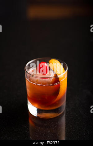 Old-fashioned cocktail on with a dark background. - Stock Photo
