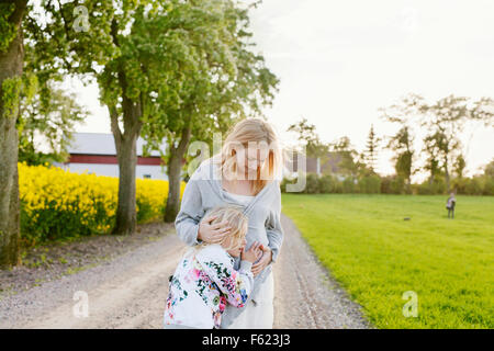 Cute girl listening to mother's pregnant belly at field - Stock Photo
