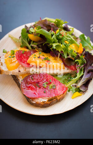 Open-faced sandwich with heirloom tomatoes and goat cheese with a side of garden greens, on a black table-top background. - Stock Photo