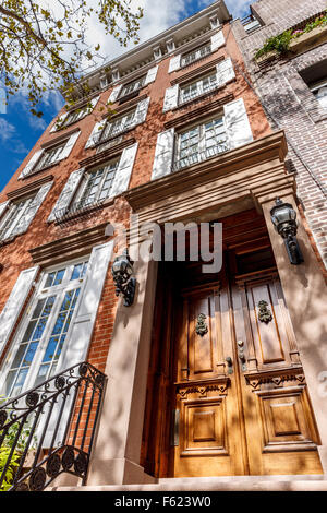 Four-storey townhouse in Chelsea, Manhattan. Typical New York City townhouse architecture with wooden door and brick - Stock Photo