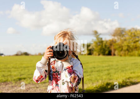 Girl photographing through SLR camera on field against sky - Stock Photo