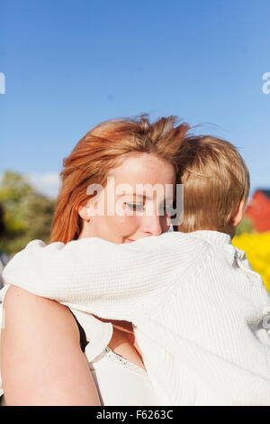 Loving mother carrying son against clear blue sky - Stock Photo