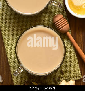 Homemade Indian Masala Chai Tea made of black tea, a variety of spices and mixed with milk, honey and ingredients - Stock Photo