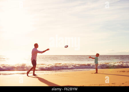 Father and Son Playing Catch Throwing Football on the Beach at Sunset - Stock Photo