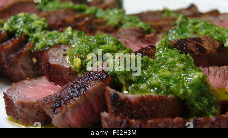 Grilled Sliced Steak and Chimichurri Sauce - Stock Photo